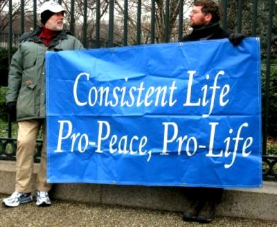 Two men hold banner that proclaims: 'Consistent Life/ Pro-Peace, Pro-Life'