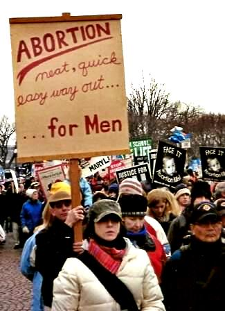Man holds sign: 'ABORTION/neat, quick easy way out......for Men'