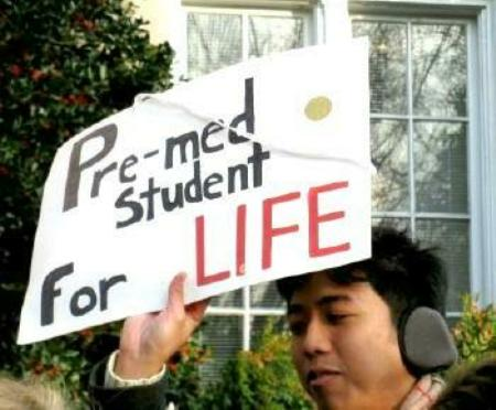Young man holds sign that says, 'Pre-med Student for Life