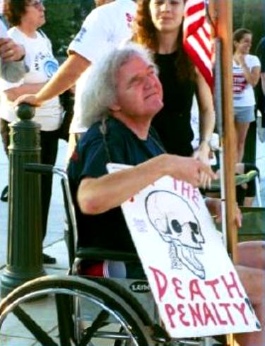 Protester in wheelchair carries anti-death penalty sign
